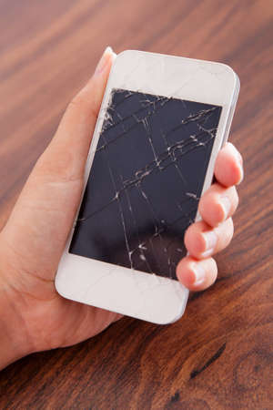 broken telephone: Close-up Of Hand Holding Smartphone With Cracked Screen Stock Photo