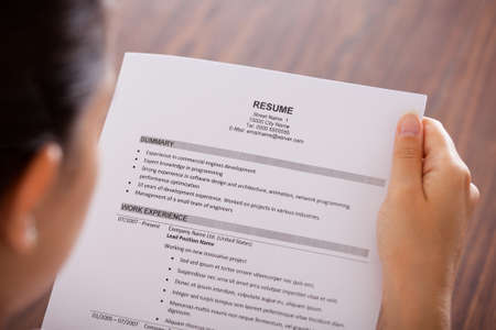 over shoulders: Close-up Of Young Businesswoman Reading Resume At Desk