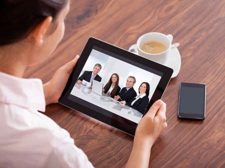 Close-up Of Woman Looking At Video Conference On Digital Tablet photo