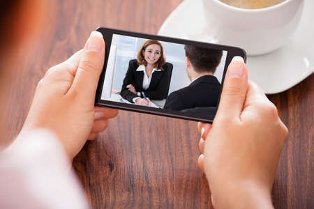 video conference: Close-up Of Woman Looking At Video Conference On Mobile Phone Stock Photo