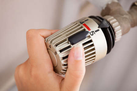 warmness: Woman Hand Adjusting The Temperature By Thermostat