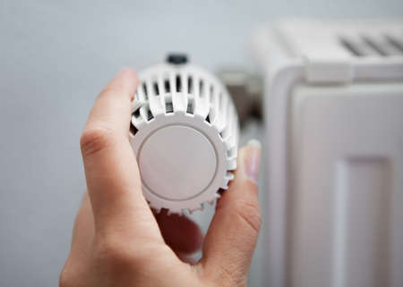 Woman Hand Adjusting The Temperature By Thermostat photo