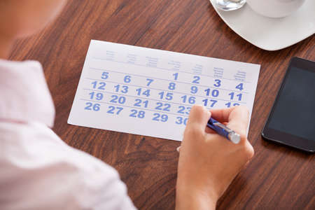 business: Close-up Of Businesswoman Marking A Day On Calendar