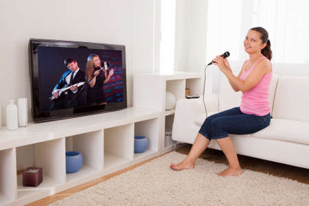 Young Woman Singing Karaoke With Microphone Looking At Television photo