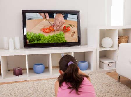 alzando la mano: Vista posterior de la mujer joven que ve la TV en el sal�n