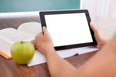 Student with apple and book on desk holding digital tablet photo