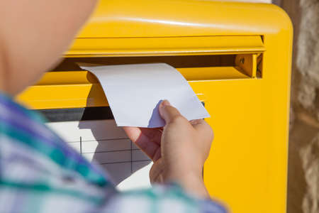 Close-up of womans hand inserting envelope in mailbox