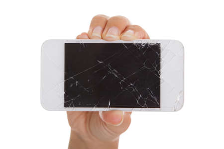 Hand holding smartphone with cracked screen over white background photo
