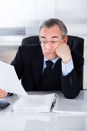 Bored Mature Businessman While Calculating At Desk photo