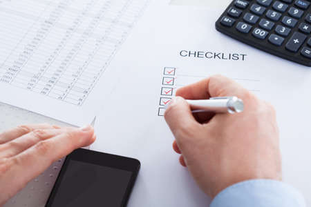 Close-up Of Hand Holding Pen Over Application Form With Mobile Phone And Calculator Stock Photo