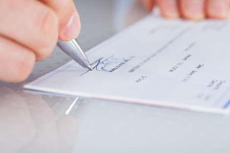chequera: Primer plano de mano que sostiene la pluma Preparación verificación de la escritura Foto de archivo