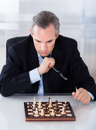 chess player: Portrait of a mature businessman playing chess