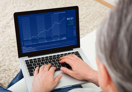 Close-up of mature man looking at stock charts Stock Photo - 22143736