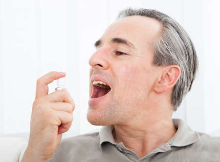 tongue: Close-up of a man applying Fresh breath spray Stock Photo