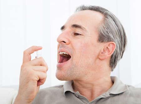 boca abierta: Primer plano de un hombre de la aplicaci�n de spray de aire fresco Foto de archivo
