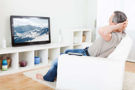 Portrait of a mature man watching tv at home photo