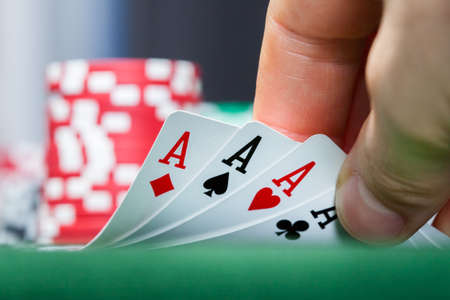 game of chance: Close-up of a poker player holding playing cards