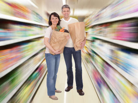 Happy couple with grocery shopping bags. Isolated on white Stock Photo - 22162762