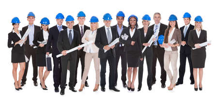 Group Of Happy Architects Holding Blue Print Over White Background photo