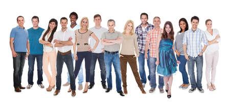 カジュアルな立っている白い背景の上に身を包んだ人々 の幸せなグループ 写真素材