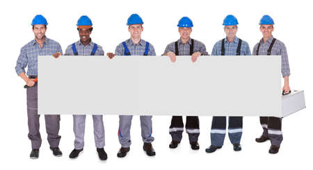Group Of Workers Holding Placard Together Over White Background photo