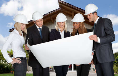Multi Ethnic Group Of Architects Looking At Blueprint In Front Of Home photo