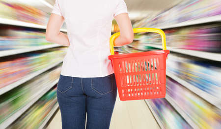 Rear View Of A Woman Holding Empty Shopping Basket In Mall photo