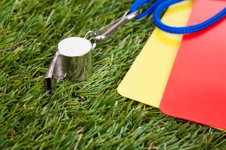 whistling: Close-up Of Whistle With Red And Yellow Card On The Field Stock Photo