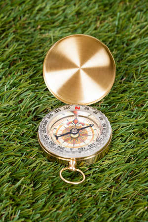 Close-up Of A Compass On Green Grass photo