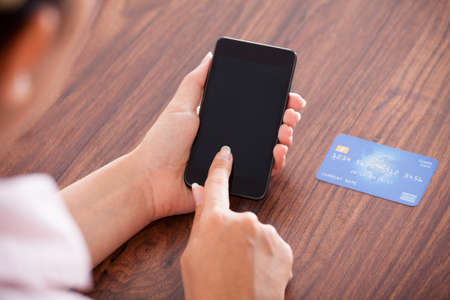 credit card bills: Close-up Of Businesswoman Paying With Credit Card On Mobile Phone