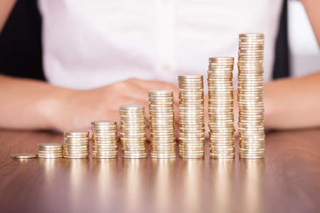 Close-up Of Businesswoman Stacking Gold Coins On Increasing Coins Stock Photo - 22306057