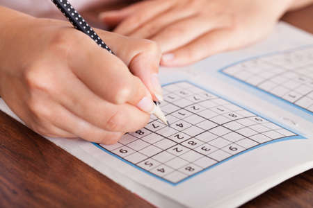 brainteaser: Close-up Of Woman Hand Solving Sudoku With Pen
