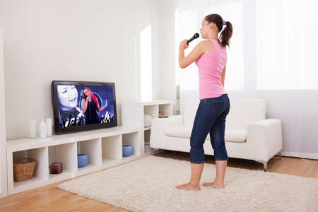 tv panel: Young Woman Singing Karaoke With Microphone Looking At Television