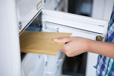 Close-up van de vrouw de hand te trekken envelop uit mailbox Stockfoto