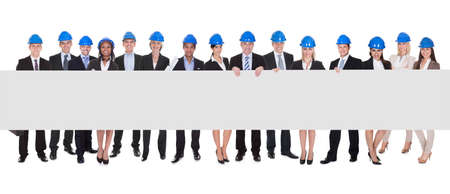 Group Of Happy Multi Ethnic Architects Holding Placard isolated over white  photo