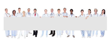 Group Of Smiling Doctors With Placard isolated over white photo