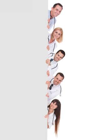 若いグループの医師を保持している空白プラカードを白で隔離されます。