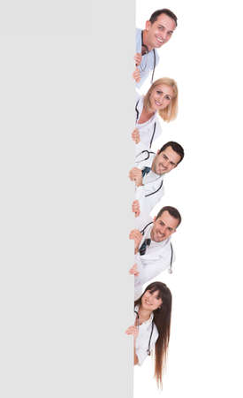 Young Group Of Doctors Holding Blank Placard isolated on white