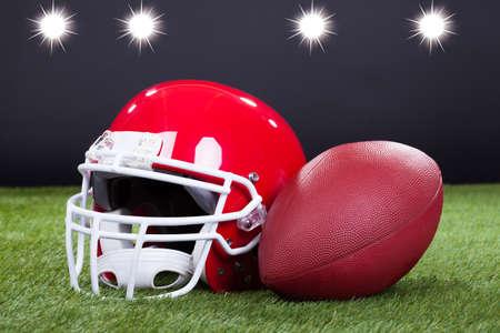 casco rojo: Red Sports Helmet miente en campo de hierba verde