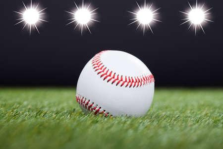 feld: Baseball On Grass Field mit Licht im Hintergrund