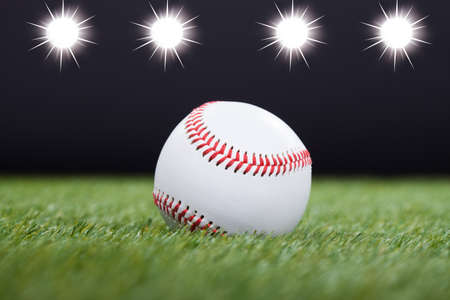baseball ball: Baseball On Grass Field With Light In The Background