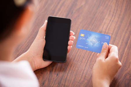 over the shoulders: Close-up Of Businesswoman Paying With Credit Card On Mobile Phone