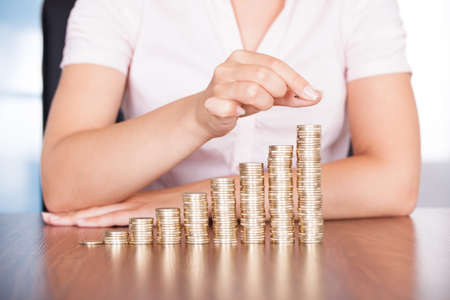 increase business: Close-up Of Businesswoman Stacking Gold Coins On Increasing Coins