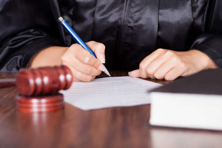 divorce court: Close-up Of Female Hand Writing On Paper In Courtroom Stock Photo