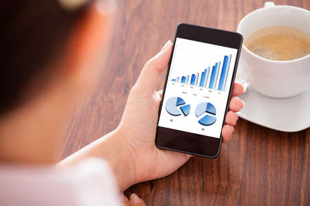 business advisor: Close-up Of Woman Looking At Graph On Mobile Phone Stock Photo