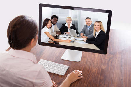 online conference: Businesswoman Sitting At A Desk Watching An Online Presentation On The Computer Stock Photo