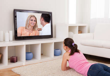 Young Beautiful Woman In Living Room Watching Television photo