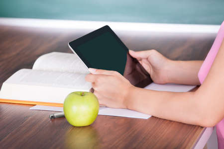 Student with apple and book on desk holding digital tablet Stock Photo