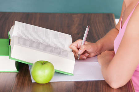 Portrait of young female student writing on paper beside green apple photo