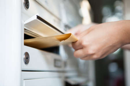 mail: Close-up of womans hand holding envelope and inserting in mailbox Stock Photo